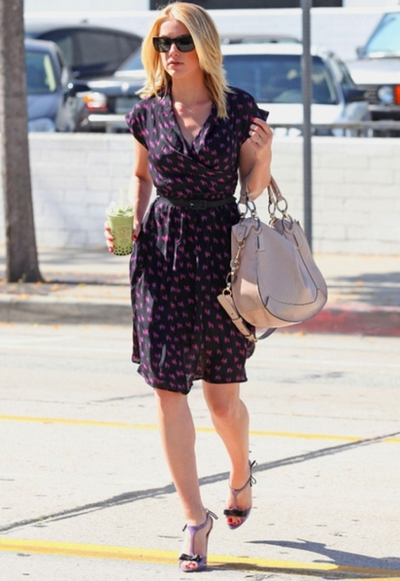 Walking by a parking lot on a sunny day, model Amber Heard was seen toting an embossed Python Tote from Coach.