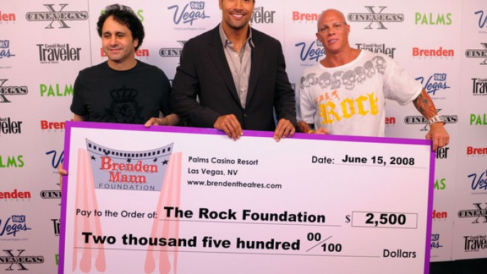 George Maloof, Dwayne Johnson, and Johnny Brenden poses with a cheque benefitting The Rock Foundation in 2008