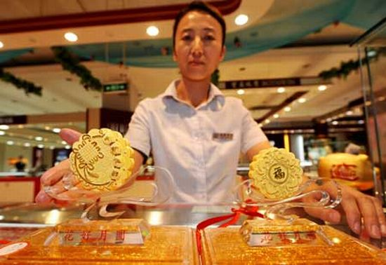 gold moon cakes on display in a department store i